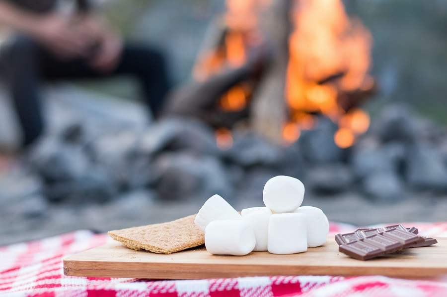 Grab and Go Quick Snacks S'mores on a Table with a Camp Fire in the Background