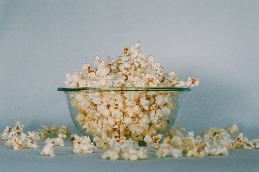 Grab and Go Quick Snacks A Glass Bowl of Popcorn with Some Spilt Out