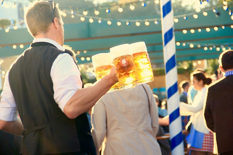 Oktoberfest Facts Man Holding Beer Walking Through an Oktoberfest Celebration