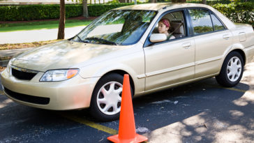 Teen girl learning to parallel park a car.