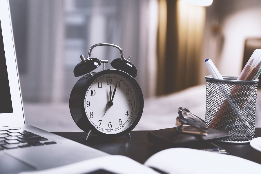 Best Time Management Tips Classic Alarm Clock on a Desk Next to an Open Book