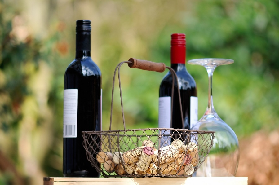 Wine Etiquette Tips Two Bottles of Red Wine with a Basket of Corks