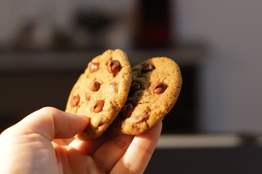 Gluten Free Chocolate Chip Cookies Recipes Person Holding Up to Cookies in One Hand
