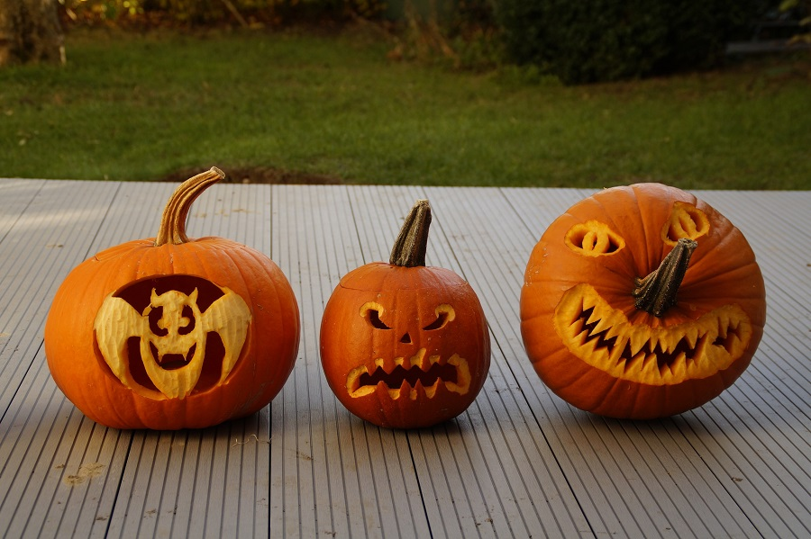 Pumpkin Carving Ideas for Halloween Three Pumpkins Carved Sitting on a PAtio