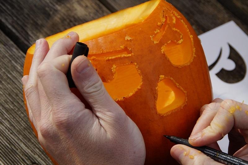 Pumpkin Carving Ideas for Halloween Close Up of an Adult Carving a Pumpkin