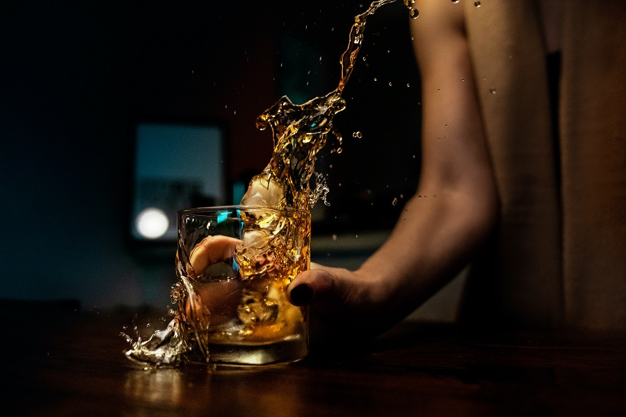 Whiskey Drinks for Summer Woman Holding a Glass of Whiskey
