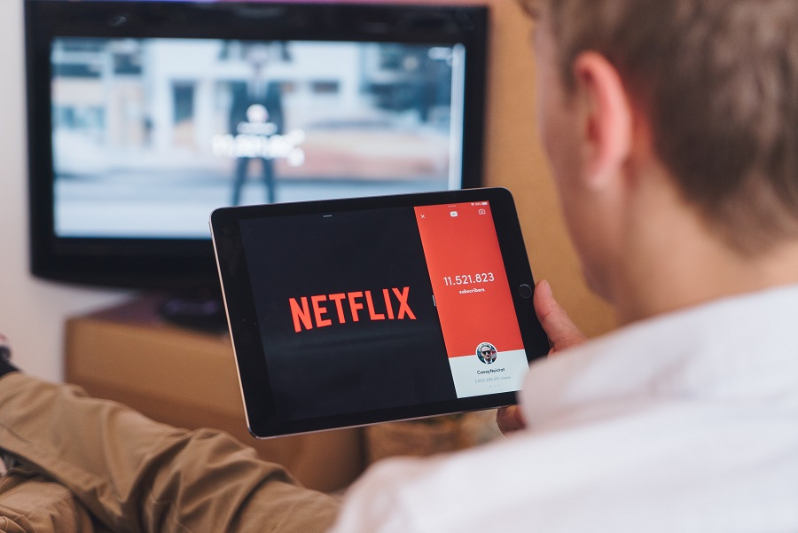 Netflix Series for Teens a Man Watching Netflix on a Tablet with a TV in the Background