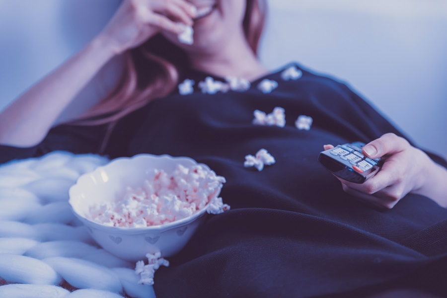Netflix Series for Teens Woman Lying in Bed Watching TV and Eating Popcorn