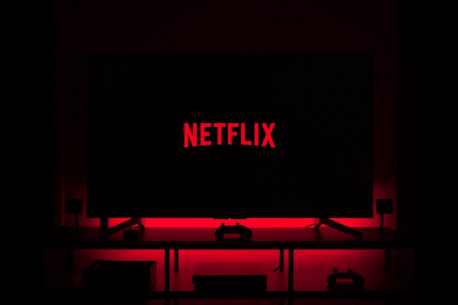 Netflix Series for Teens a TV in a Dark Room with the Netflix Logo on it and a Red Light Behind the TV