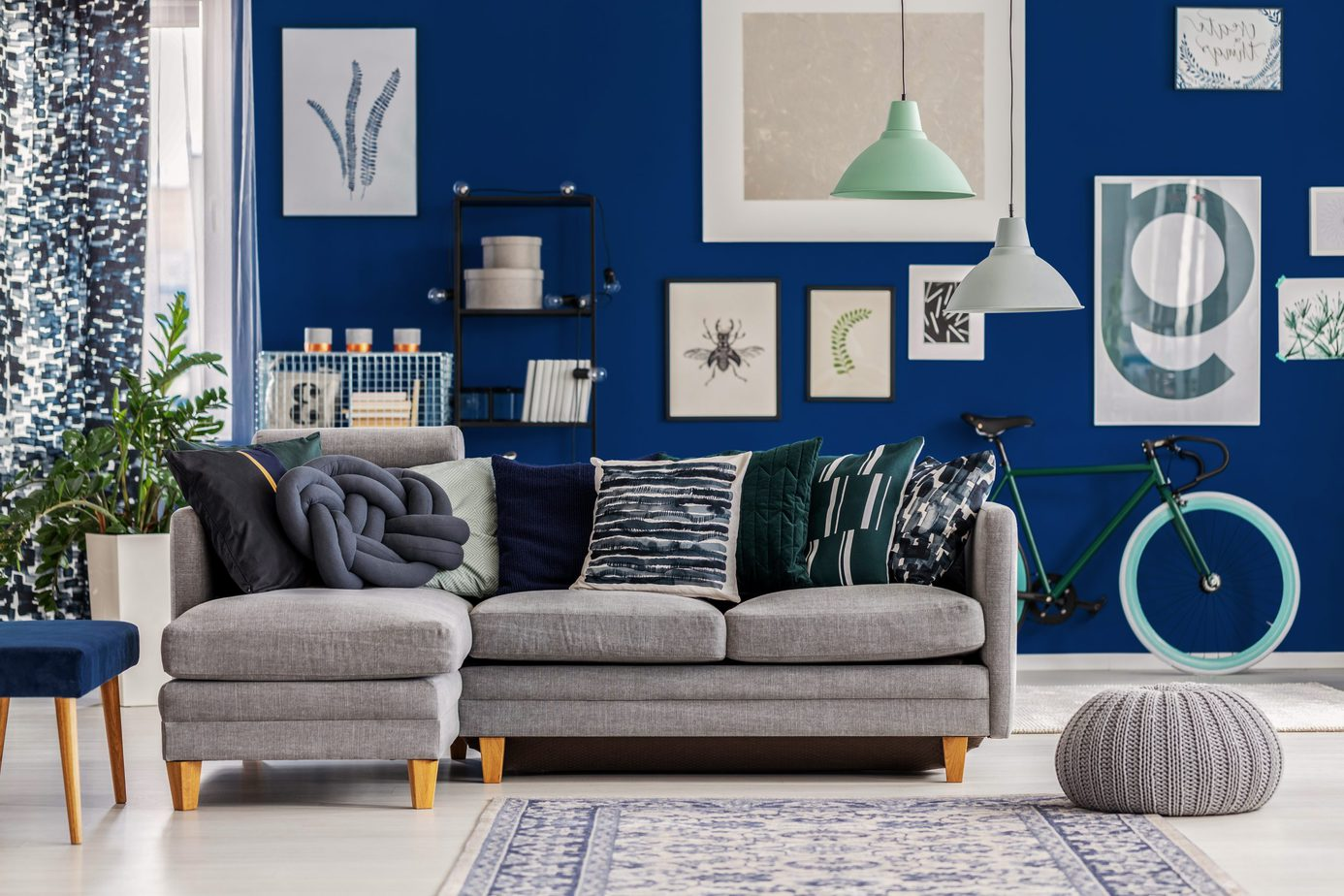 Grey and mint lamps above pouf and corner sofa with pillows in blue interior with posters on the wall