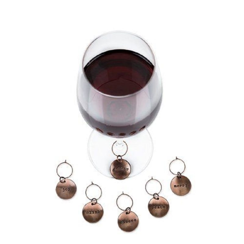 Brushed Copper Holiday Wine Charms on a Wine Glass Filled with Red Wine