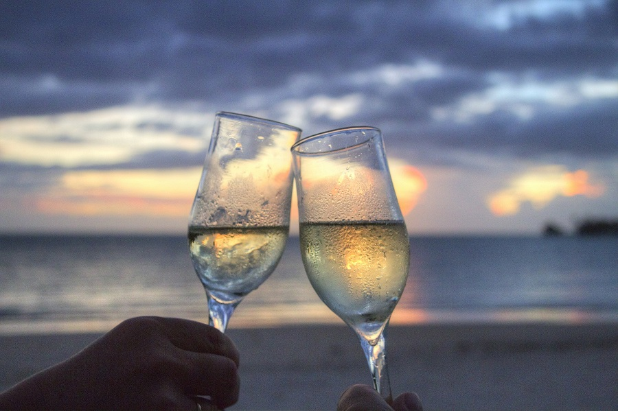 Funny Drinking Toasts Two Glasses Clinking Together in Front of a Sunset on a Beach