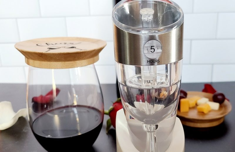 Stainless Steel Luxury Adjustable Wine Aerator On a Black Counter Top with a Half Filled Glass of Wine with Cheese and Fruit Nearby
