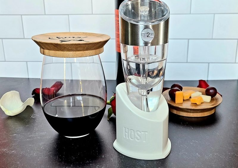 Stainless Steel Luxury Adjustable Wine Aerator On a Counter with a Half Filled Wine Glass and Wine Topper Next to it