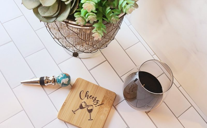 Cheers Cocktail and Wine Wooden Coasters on a Countertop with a Glass of Wine and a Wine Stopper