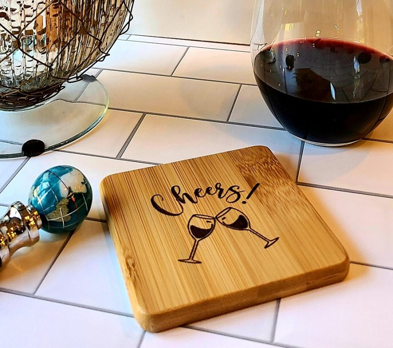 Close Up of the Cheers Cocktail and Wine Wooden Coasters with a Glass of Wine in the background and a Wine Stopper