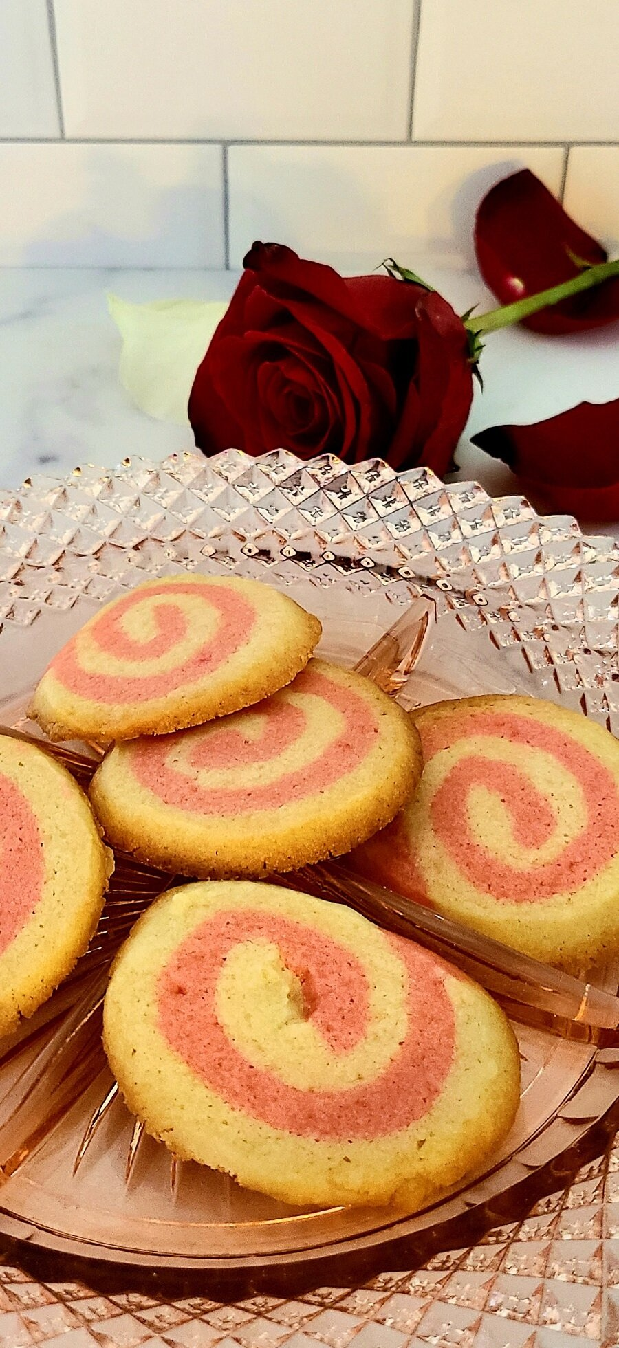 Pink Pinwheel Sugar Cookies Close Up of Cookies on a Plate with a Rose Behind It