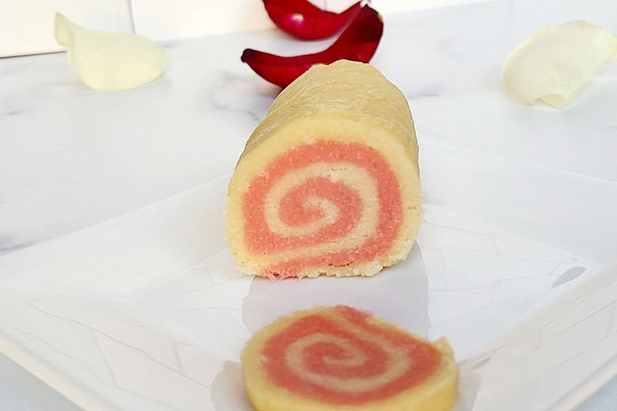 Pink Pinwheel Sugar Cookies Front View of a Log of Dough With a Slice Cut Out