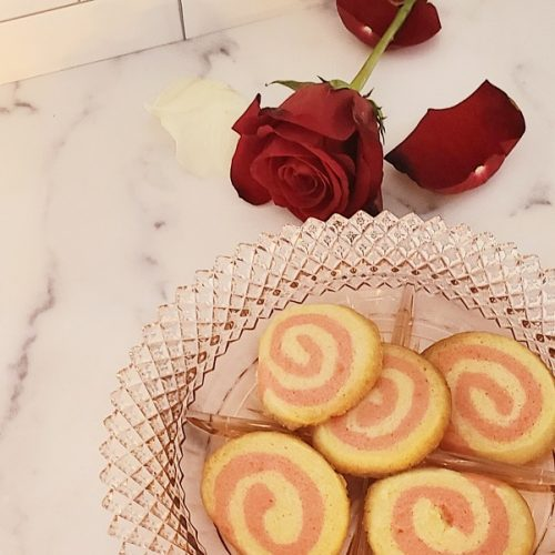 Pink Pinwheel Sugar Cookies on a Plate with a Rose Next to the Plate on a Marble Counter Top