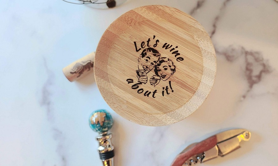 Wine Glass Toppers Overhead View of a Topper on a Wine Glass That Says Let's Wine About It!