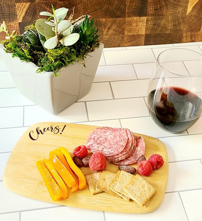 Angled View of a Personalized Mini Charcuterie Board with Meat and Fruit and a Wine Glass Filled with Red Wine