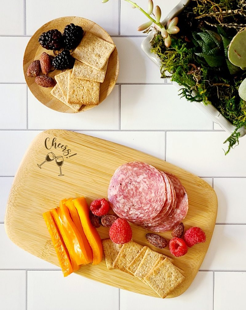 Overhead View of a Personalized Mini Charcuterie Board with Meat and Fruit and a Wine Glass Topper with Fruit and Crackers on White Tile