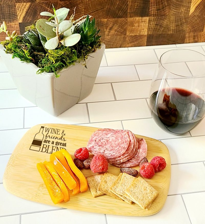 Personalized Mini Charcuterie Board Angled View of a Cheese Board with Meat, Crackers, and Cheese and a Glass of Wine