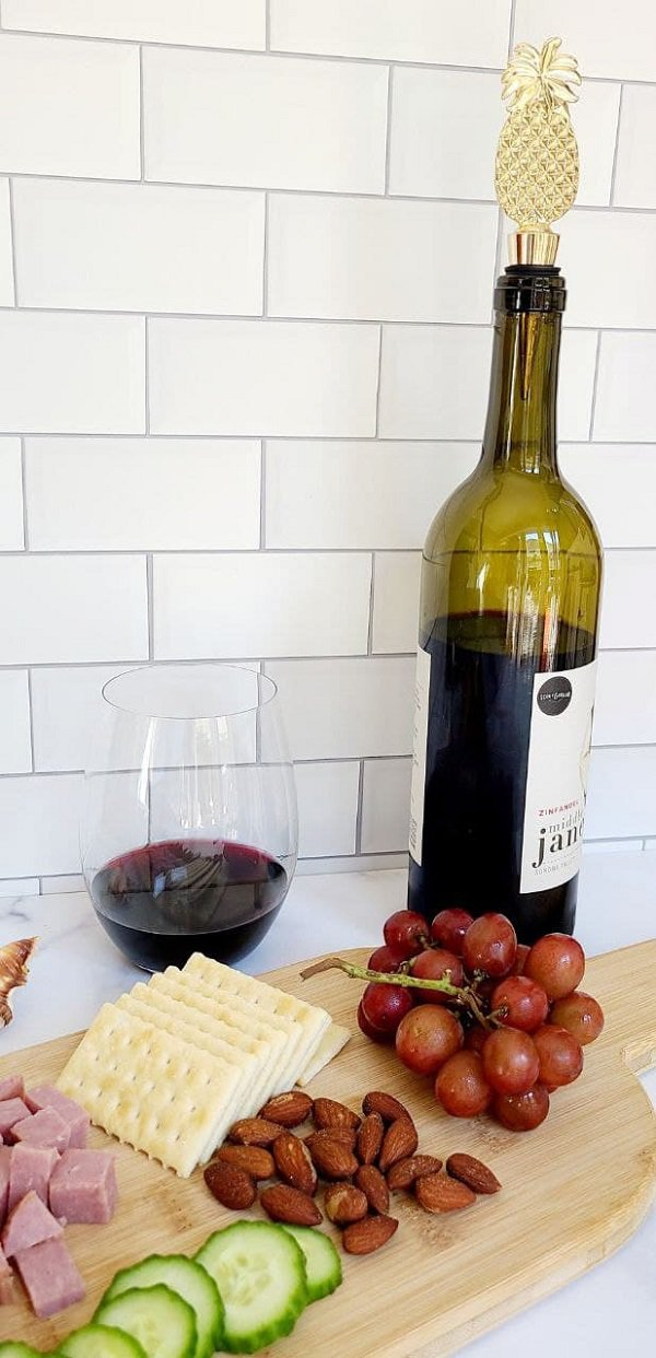 Aloha Pineapple Bottle Stopper in a Wine Bottle Next to a Cheese Board with Grapes and Cheeses