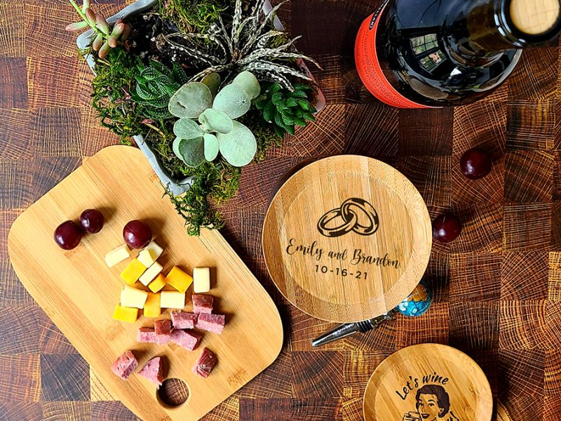 Personalized Wedding Favor Engraved Wine Glass Topper Overhead View of Topper on a Wine Glass with a Charcuterie Board Next to it